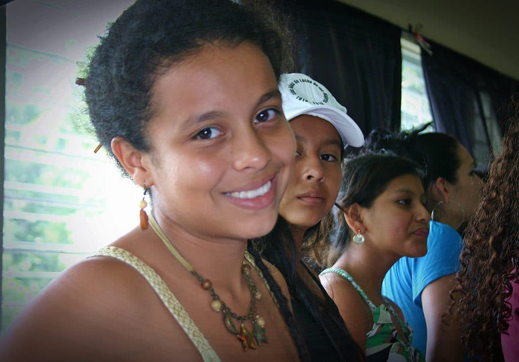 Picture of a young woman with short hair from El Salvador looking into the camera from the side.