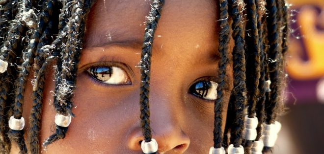 A child with decorated braids looks thoughtfully into the camera.