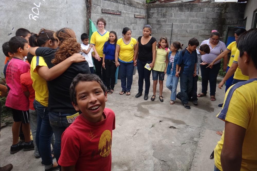 Kinder und Jugendliche stehen im Hinterhof eines Hause im Kreis und halten gegenseitig ihre Hände. Manche von ihnen haben blau-gelbe T-Shirts angezogen.