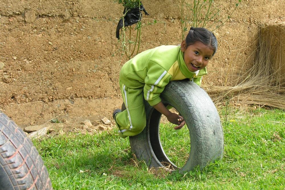 A girl is lying on a car tire.