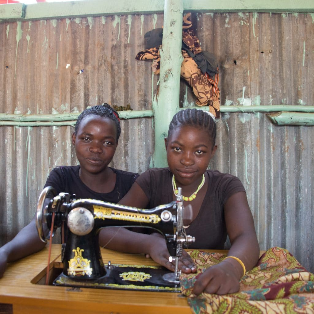 Zwei junge schwarze Frauen sitzen hinter einer alten Singer-Nähmaschine.
