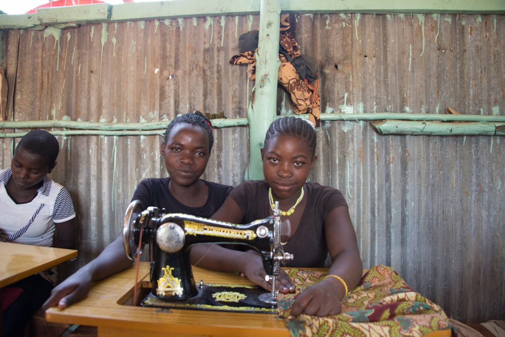 Two young black women sit behind an old sowingmachine.