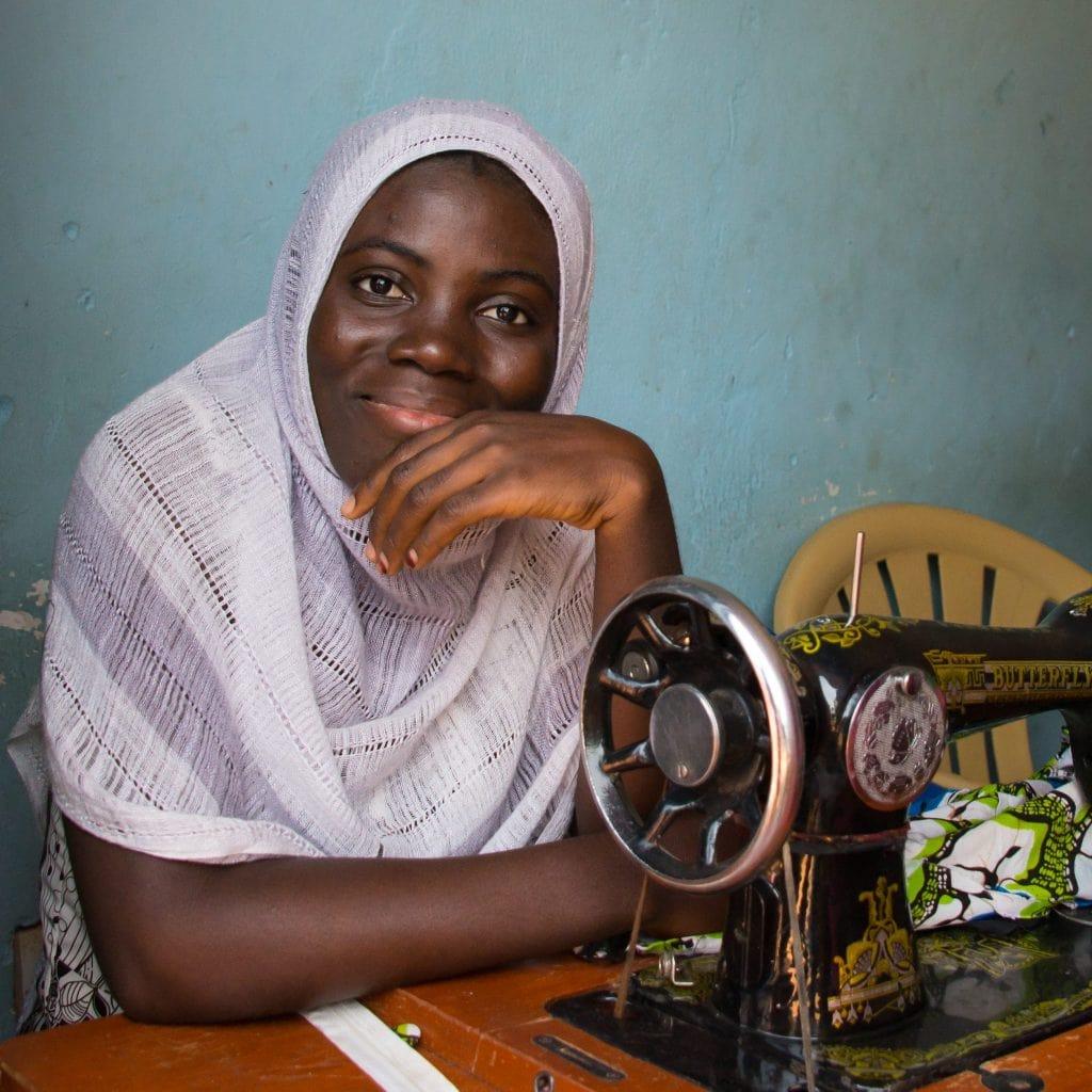 Junge schwarze Frau an einer alten, pedalbetriebenen Nähmaschine.