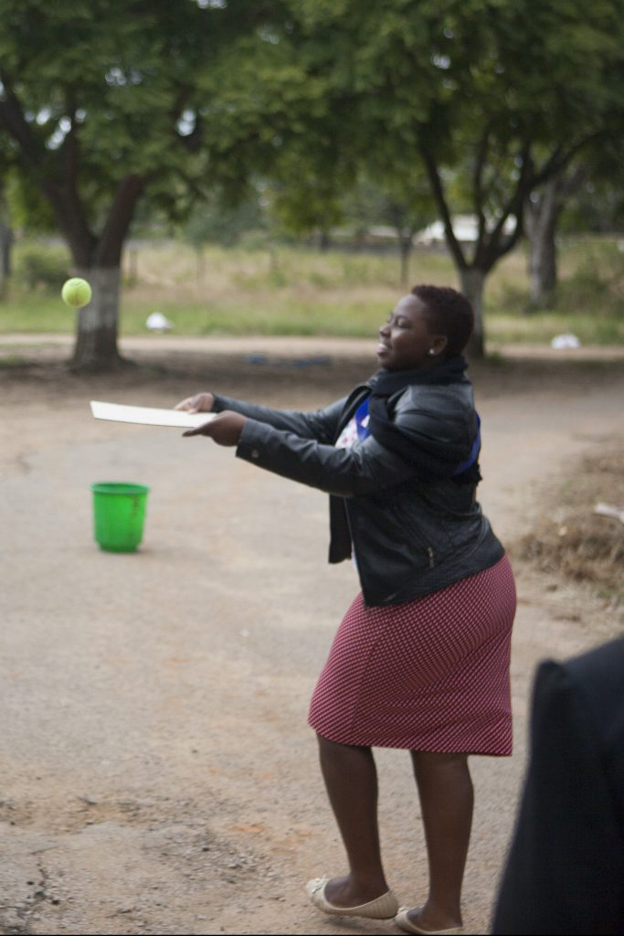 Zwei Frauen blancieren einen Tennisball mit einem Stück Karton in der Hand. Sie werfen sich mit dem Karton den Tennisball gegenseitig zu.