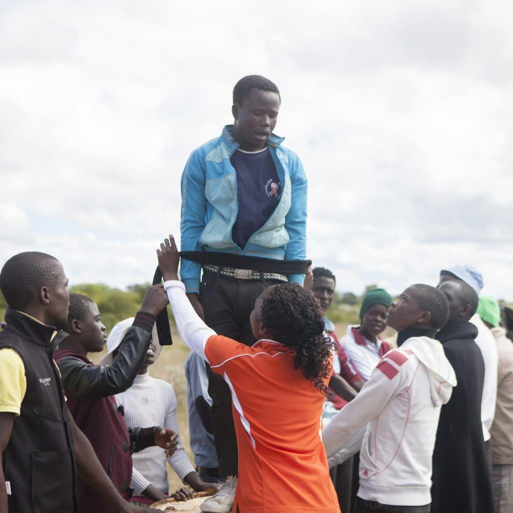 Ein schwarzer Jugendlicher steht auf einem Podest und wird mit einem schwarzen Band gefesselt. Andere Jugendliche stehen zu seiner Absicherung um ihn herum.