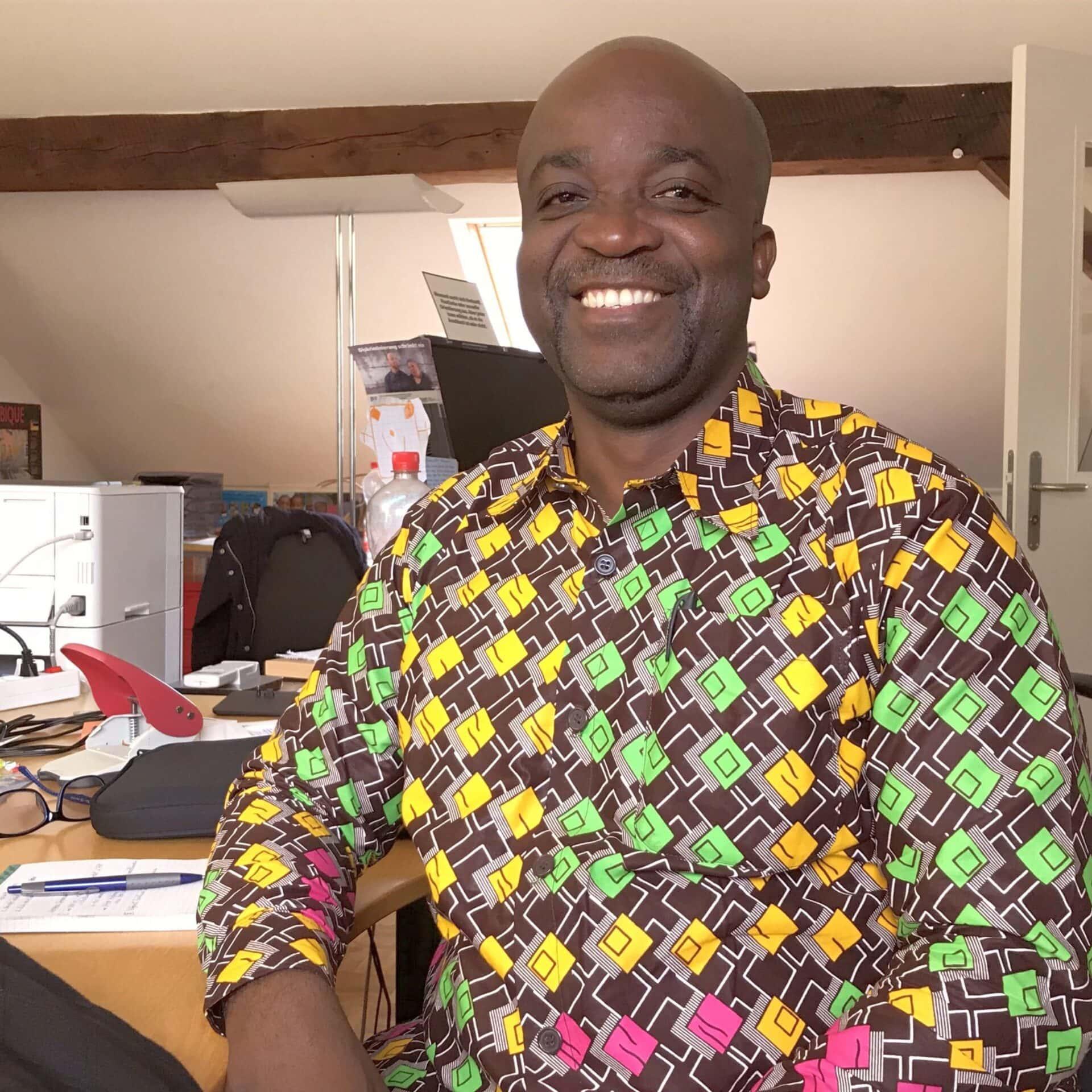 Nahaufnahme von Abubakar Mutoka Balibanga. Er sitzt an einem Tisch im Büro in Basel.