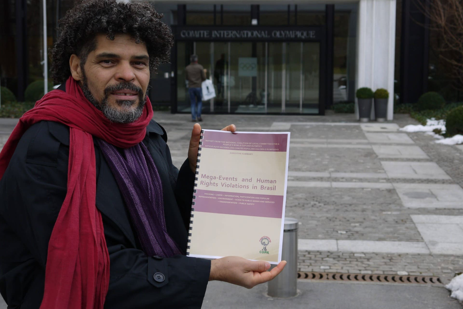 Argemiro vor dem Eingang zum Internationalen Olympischen Komitee. Er hält einen Bericht mit dem Titel: Mega-Events and Human Rights Violations in Brasil.