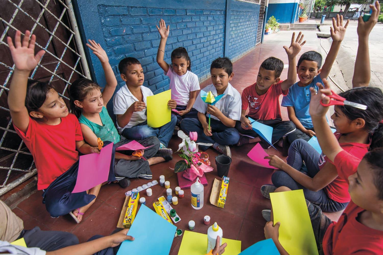 Kinder sitzen gemeinsam in einem Kreis und schreiben oder Basteln.