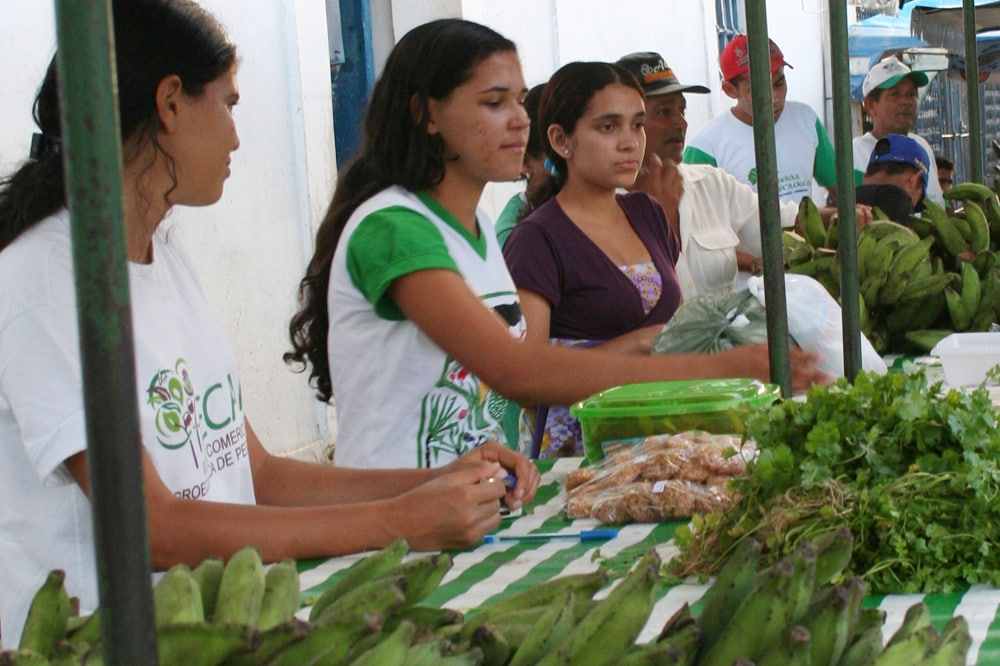 Young women sell their own bananas at the market stall.