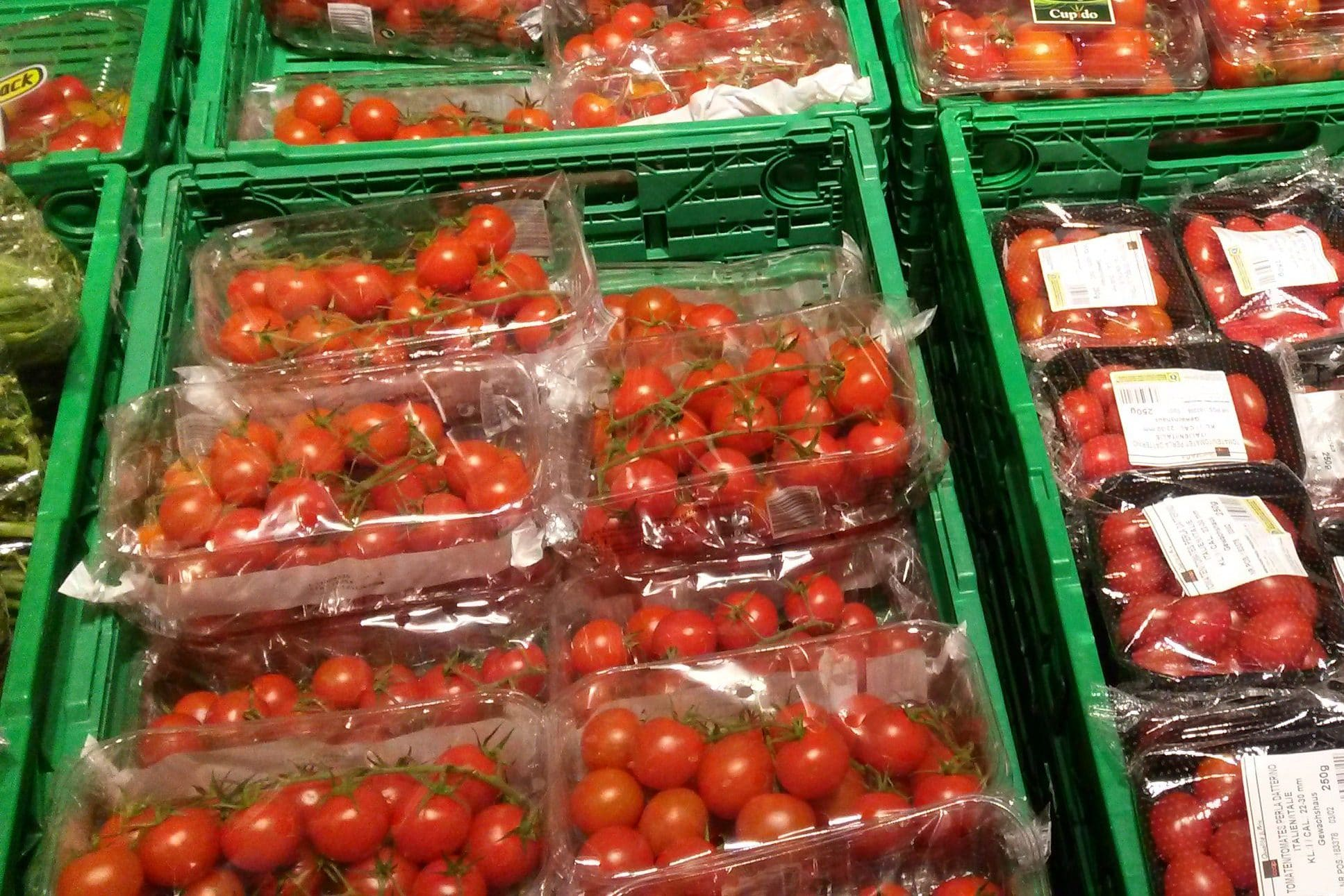 Cherrytomaten mit Plastikverpackung in Harassen in einem Supermarkt.