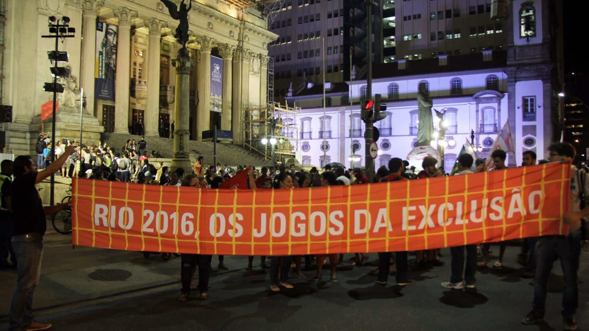 Demonstrators in front of the Parlemts building in Rio with a poster with the inscription: Rio 2016 - Os Jogos da Exclusao.