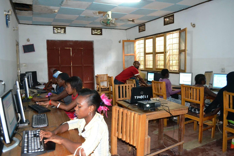 Junge schwarze Frauen sitzen in einer Reihe an Tastaturen und Bildschirmen auf einfachen Holzstühlen.