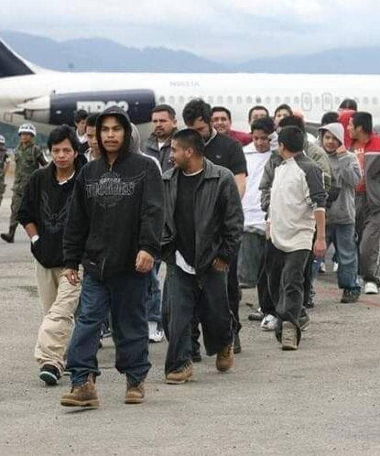 Junge lateinamerikanische Männer vor einem Flugzeug. Sie laufen in einer Reihe.