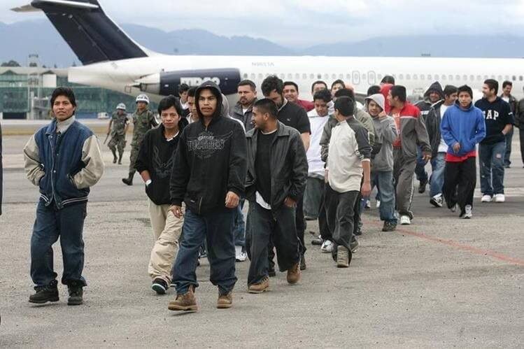 Young latin american men in front of a plane. They walk in a row.