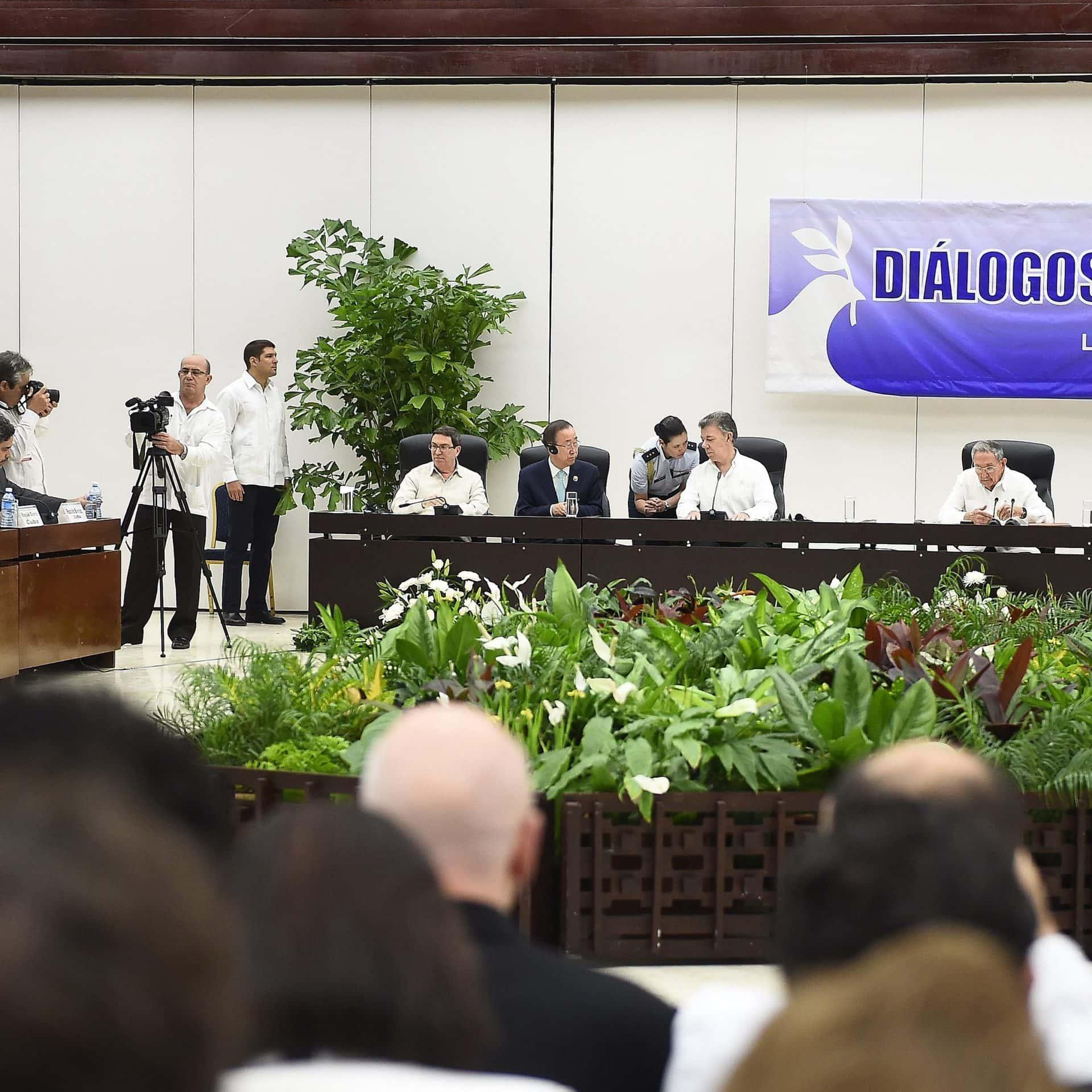 Männer mit weissen Hemden sitzen an einem langen Konferenztisch.