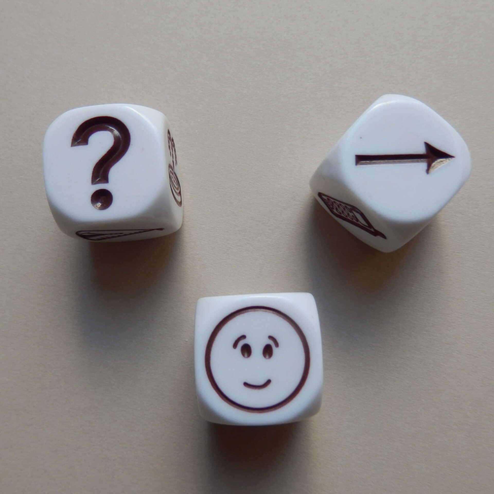 Three white cubes with one black icon each: a question mark, a smiley face and an arrow pointing to the right.