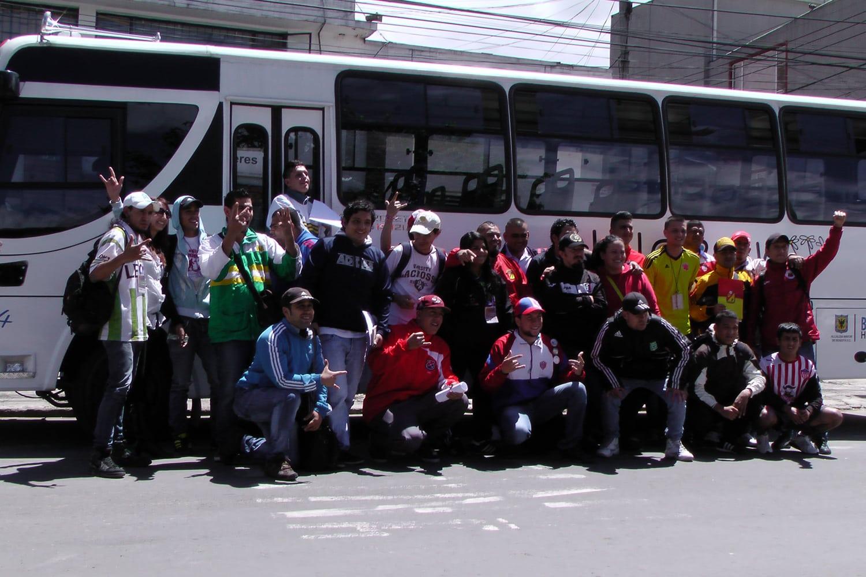 25 Jugendliche von 18 Fanklubs und der FJMBN stehen für ein Gruppenfoto zusammen vor einem weissen Autobus.