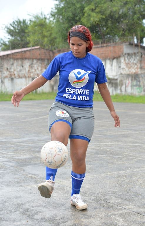 A teenager juggles a white football with her foot.