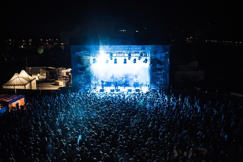 Blau beleuchtete Bühne in der Dunkelheit, links davon ein normal beleuchteter Pavillion.