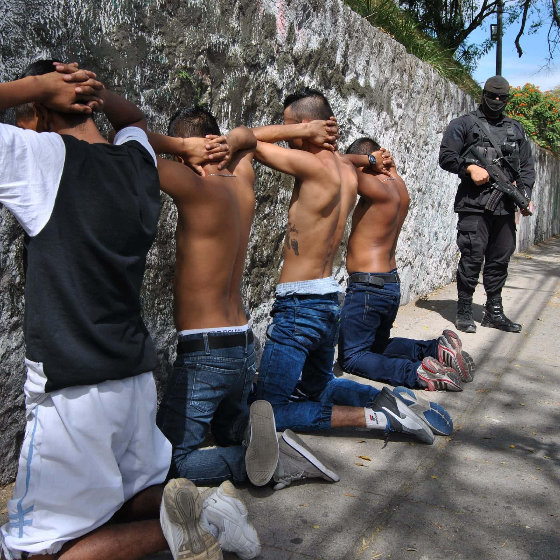 Ein vermumter Polizist in Schwarz und mit Maschinenpistole bewacht vier Jugendliche