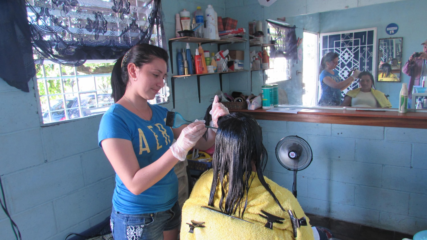 A young woman dyes hair in a hair studio.
