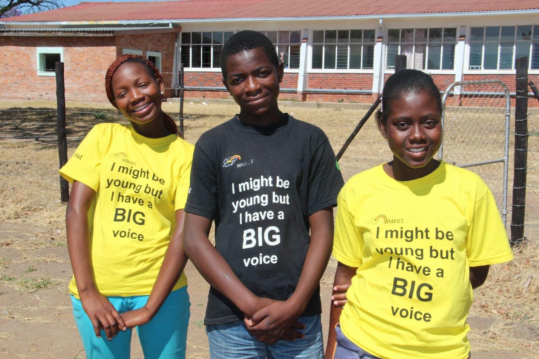 Drei Jugendliche mit schwarzen und gelben T-Shirts. Aufdruck: I might be young but I have a BIG voice.