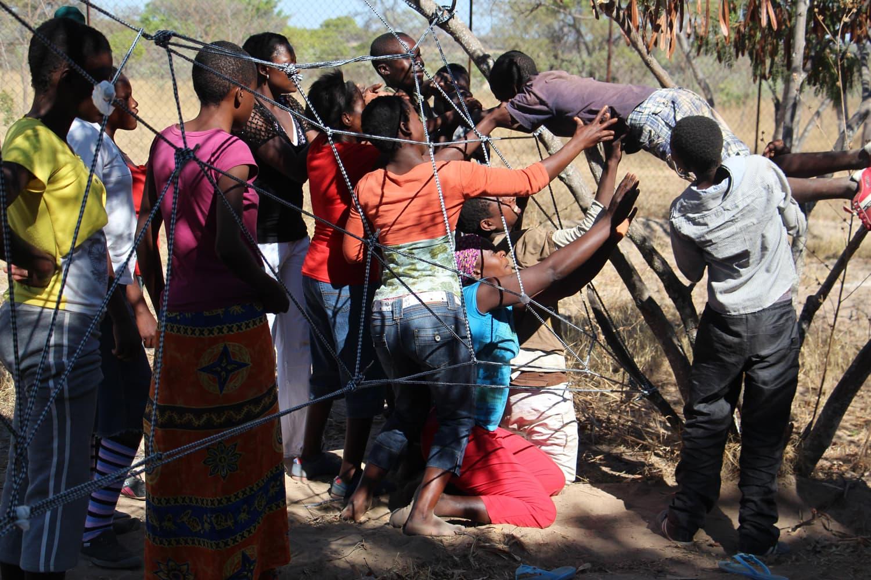 Ein Jugendlich wird Hilfe seiner Freunde durch einen spinnennetzartigen Seilaufbau hindurchgereicht.