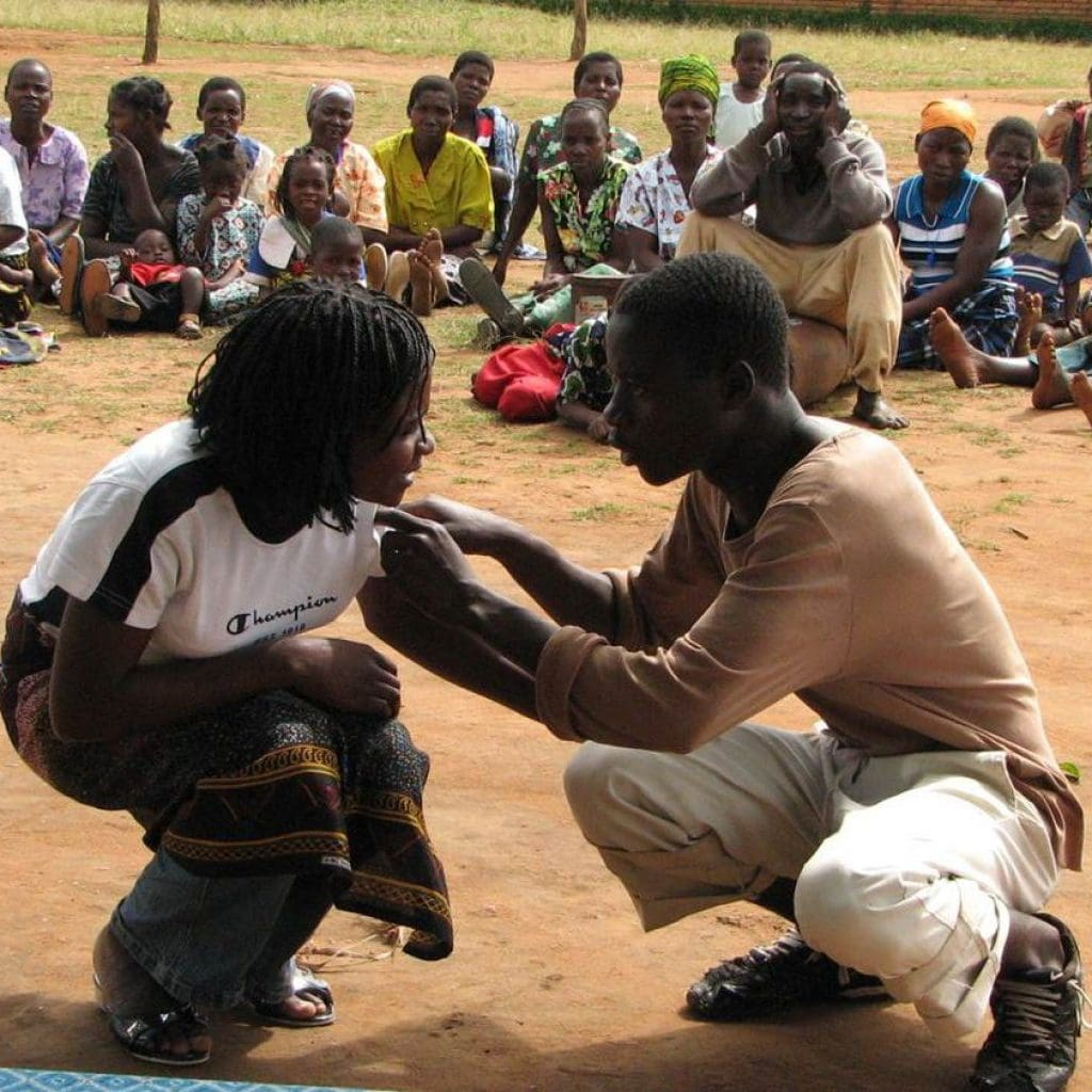 Two young people perform a theatre scene in front of an audience.
