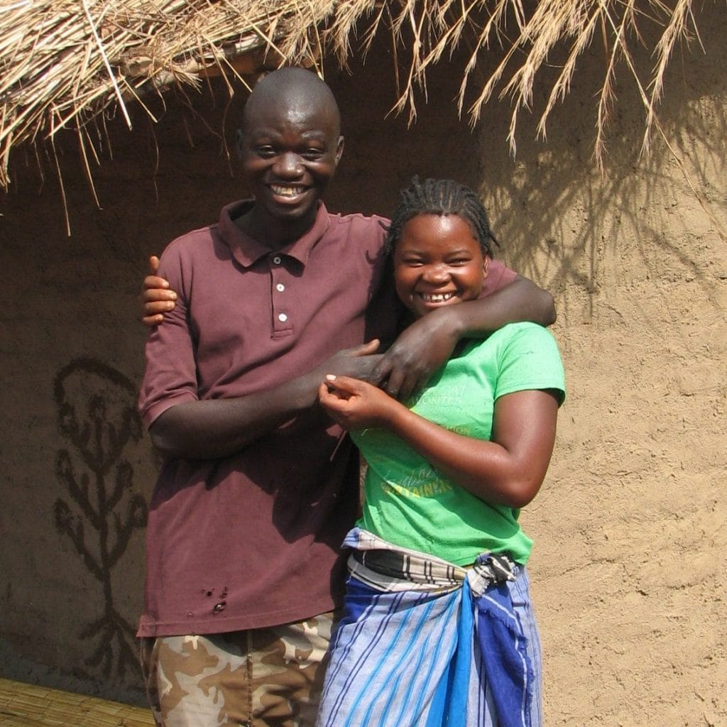 A young couple from Mozambique in front of their own house.