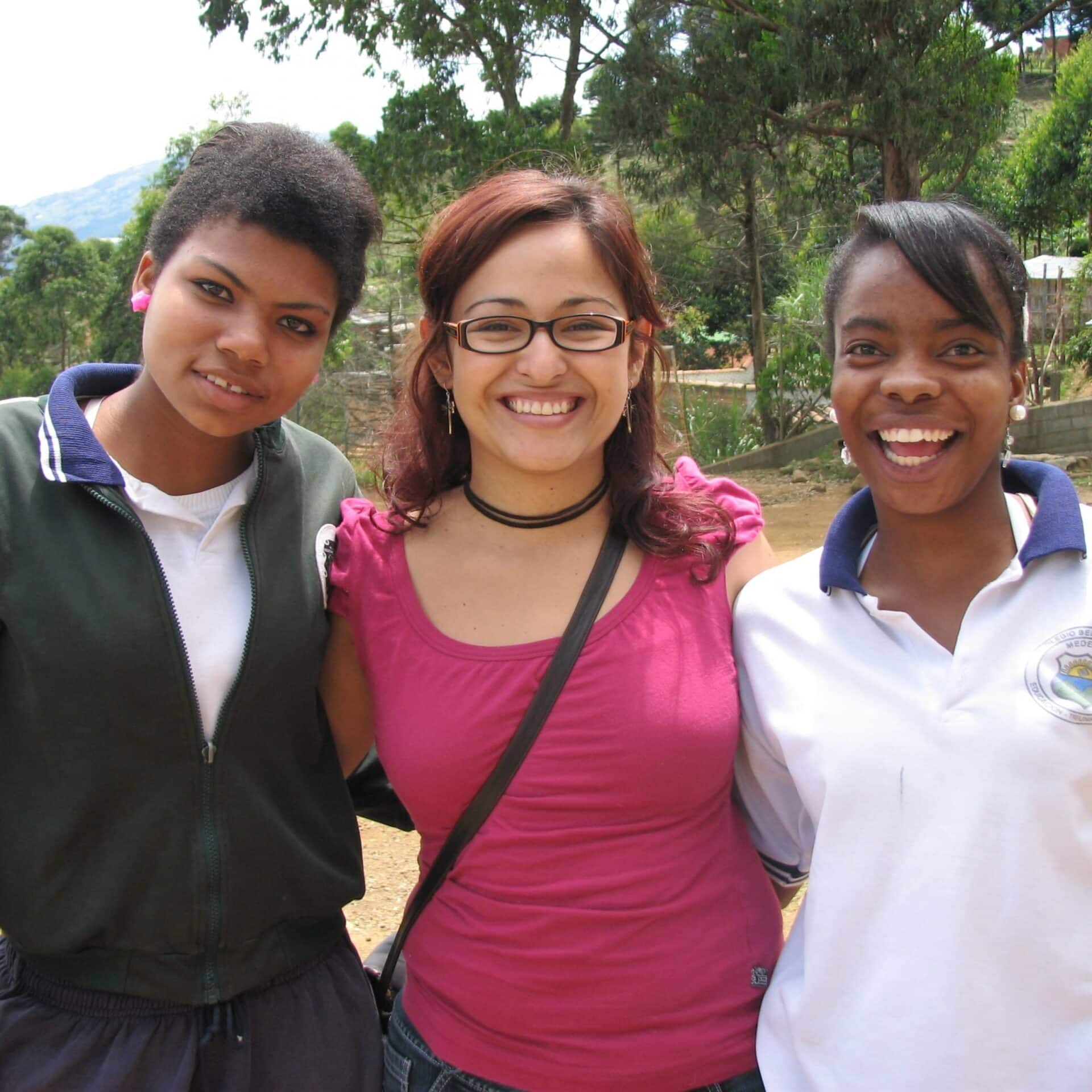 Three young women from Antioquia, Colombia stand arm in arm smiling.