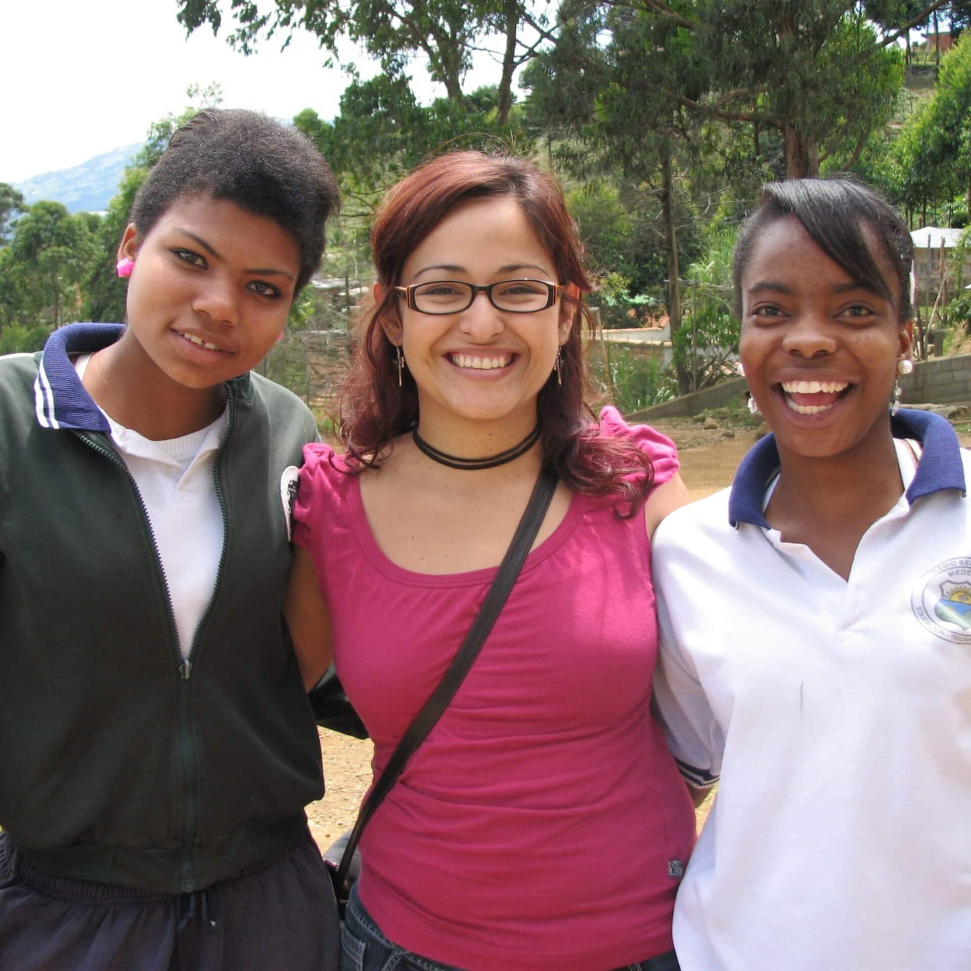 Drei junge Frauen aus Antioquia, Kolumbien stehen Arm in Arm lächelnd.
