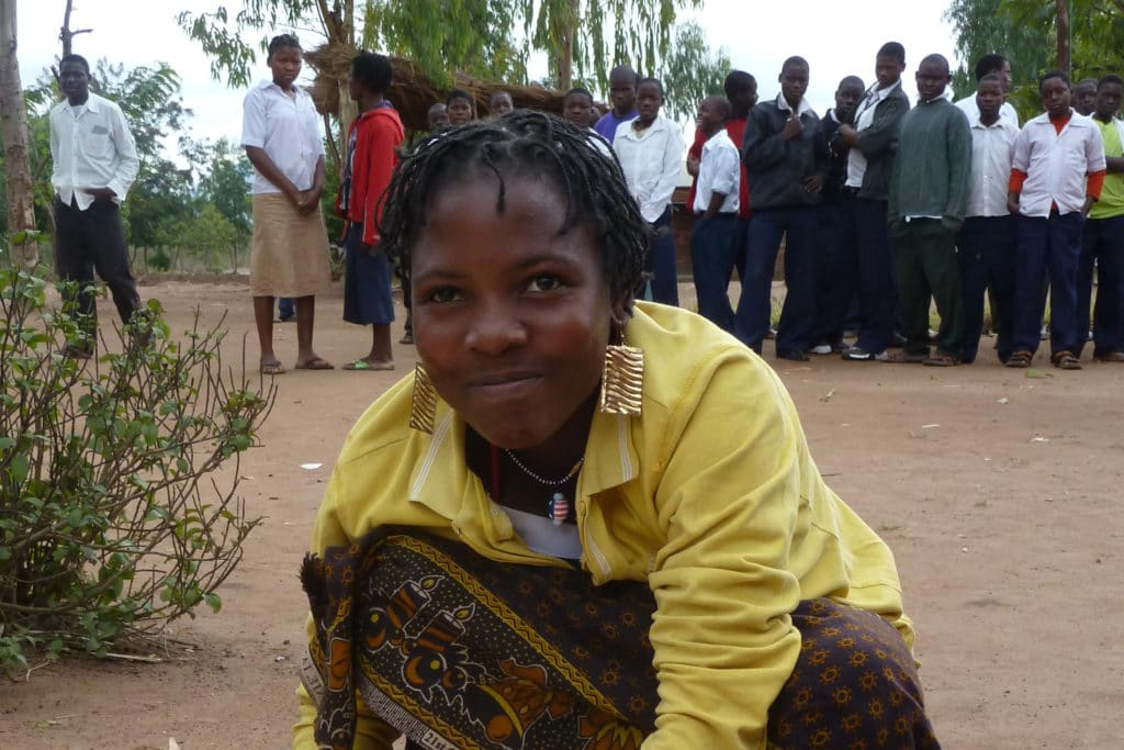 Eine junge Frau aus Moçambique flechtet Schilfrohr.