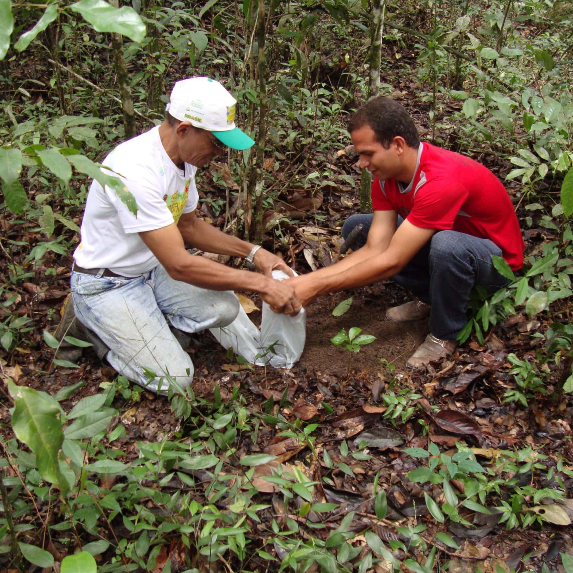 Ein Mann und ein Jugendlicher knien auf dem Boden und füllen Erde in einen Plastiksack.