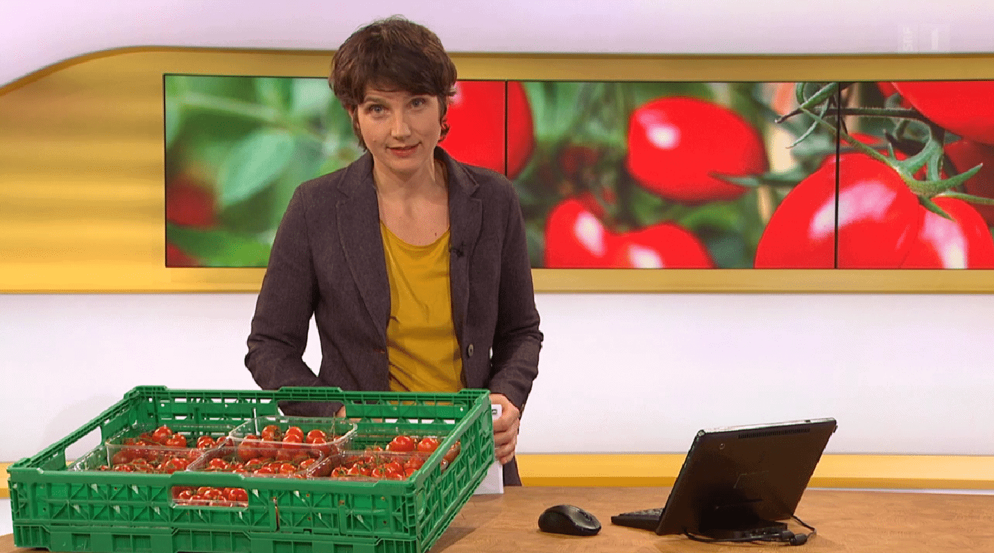 Screenshot from the program Kassensturz. The presenter has tomatoes on the table.