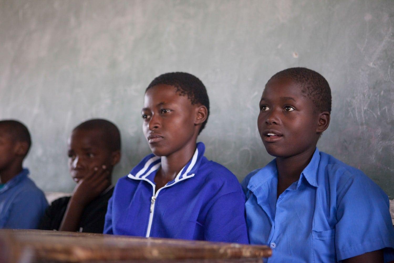 Mädchen mit blauen Schuluniformen schauen konzentriert an der Kamera vorbei.