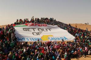 Viele Sahraouis stehen um eine riesige Fahne mit der Aufschrift: Siemens get out of Western Sahara.