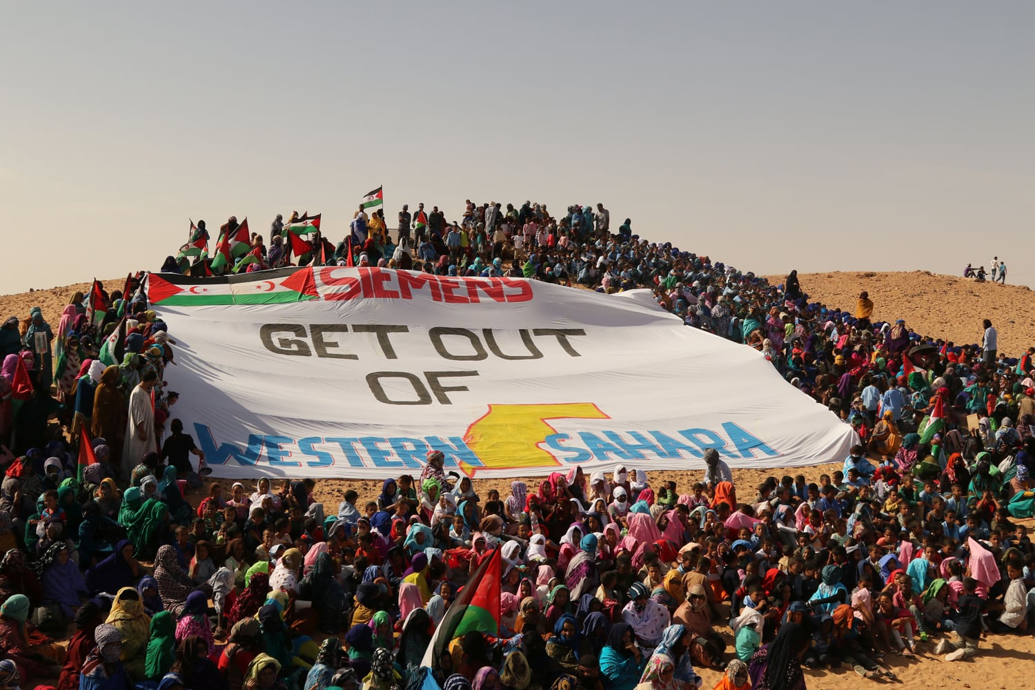 Many Sahrawis stand around a huge flag with the inscription: Siemens get out of Western Sahara.