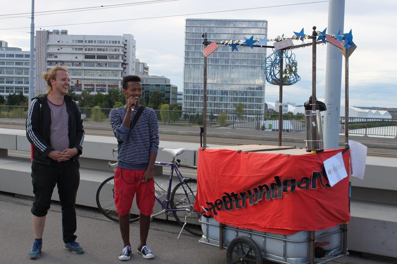 Schwarzer Teenager beim Stadtrundgang auf der Dreirosenbrücke. Hinter ihm steht ein Velo mit Wagen.