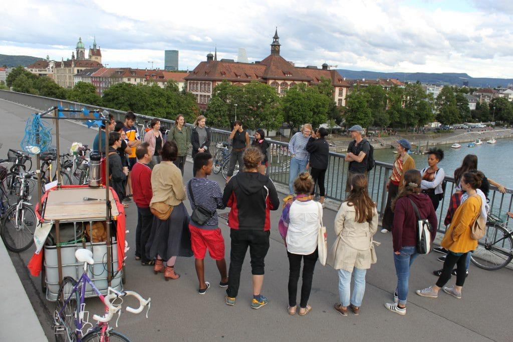 Ein Kreis von Menschen auf der Dreirosenbrücke.