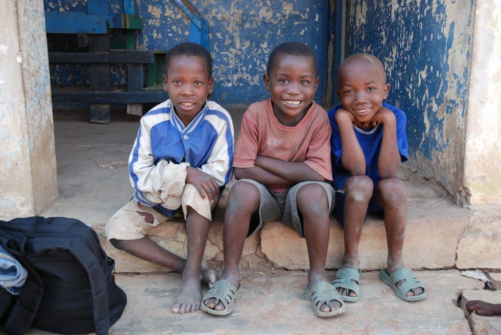 Drei schwarze Buben aus Tansania sitzen auf einer Türschwelle.