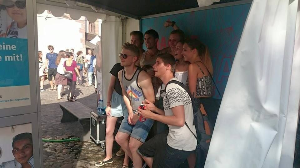Jugendliche stehen im Zelt vor der Fotobox und lassen sich gemeinsam fotografieren.