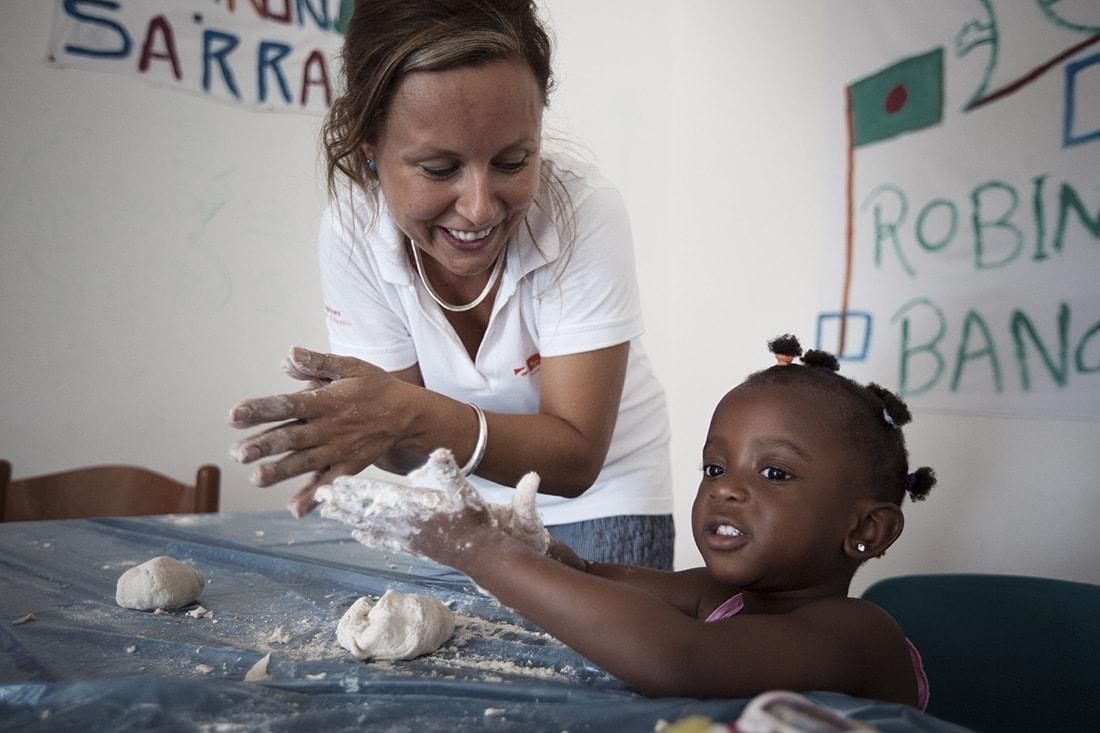 Ein Projektmitarbeiterin von FARO knetet mit einem schwarzen Mädchen einen Teig.