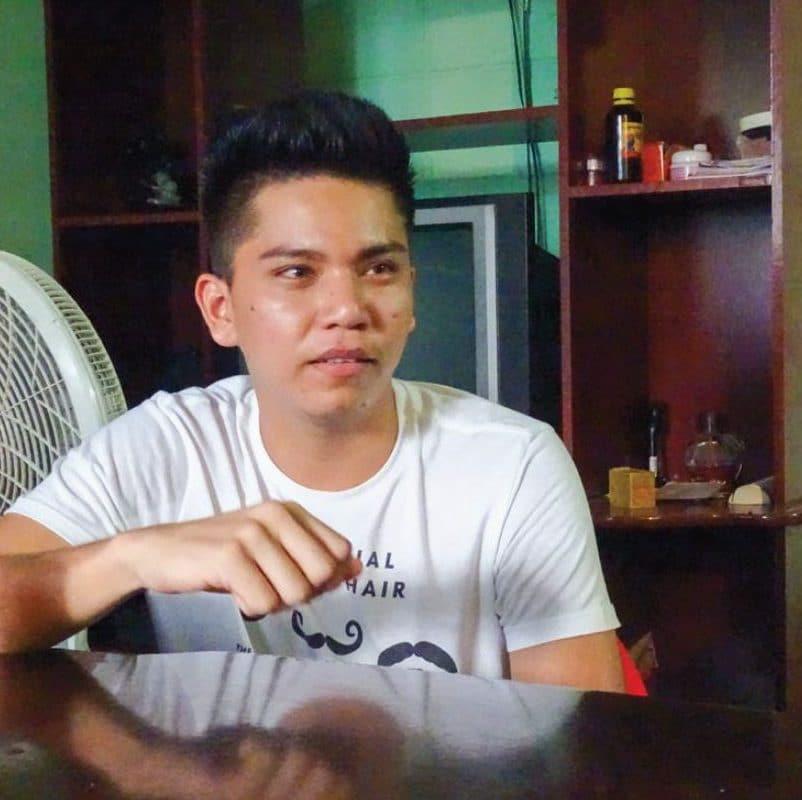 Junger Mann mit weissem T-Shirt, der an einem dunklen Holztisch sitzt.