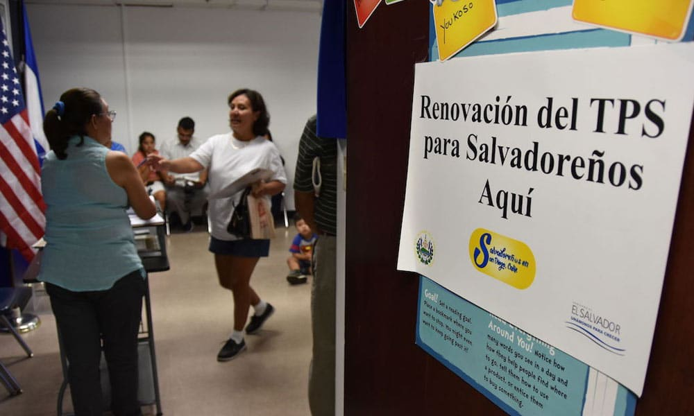 Schild mit spanischer Inschrift. Im Hintergrund Menschen und eine amerikanische Flagge