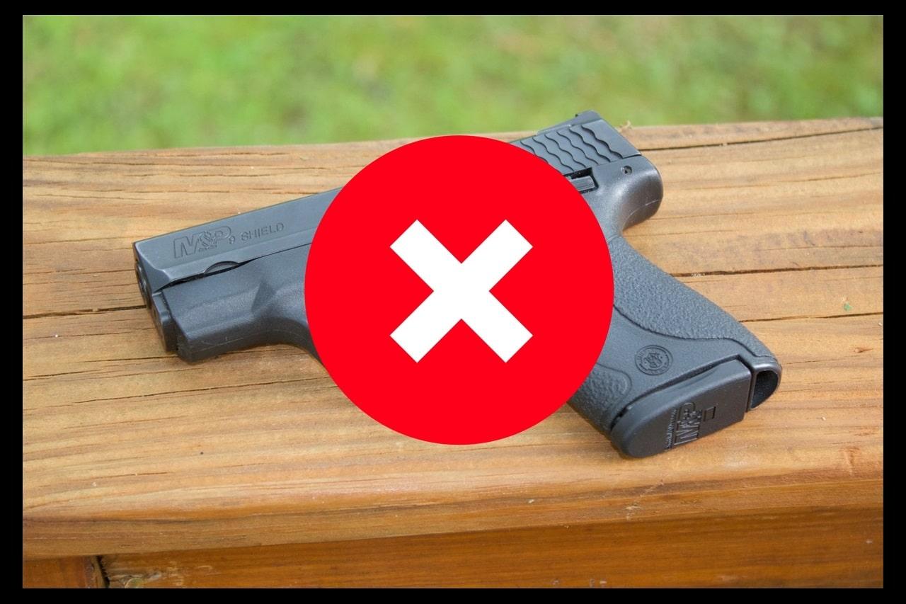 Eine Handfeuerwaffe auf eine Holzgeländer. Darüber ein grosses X mit roter Farbe.