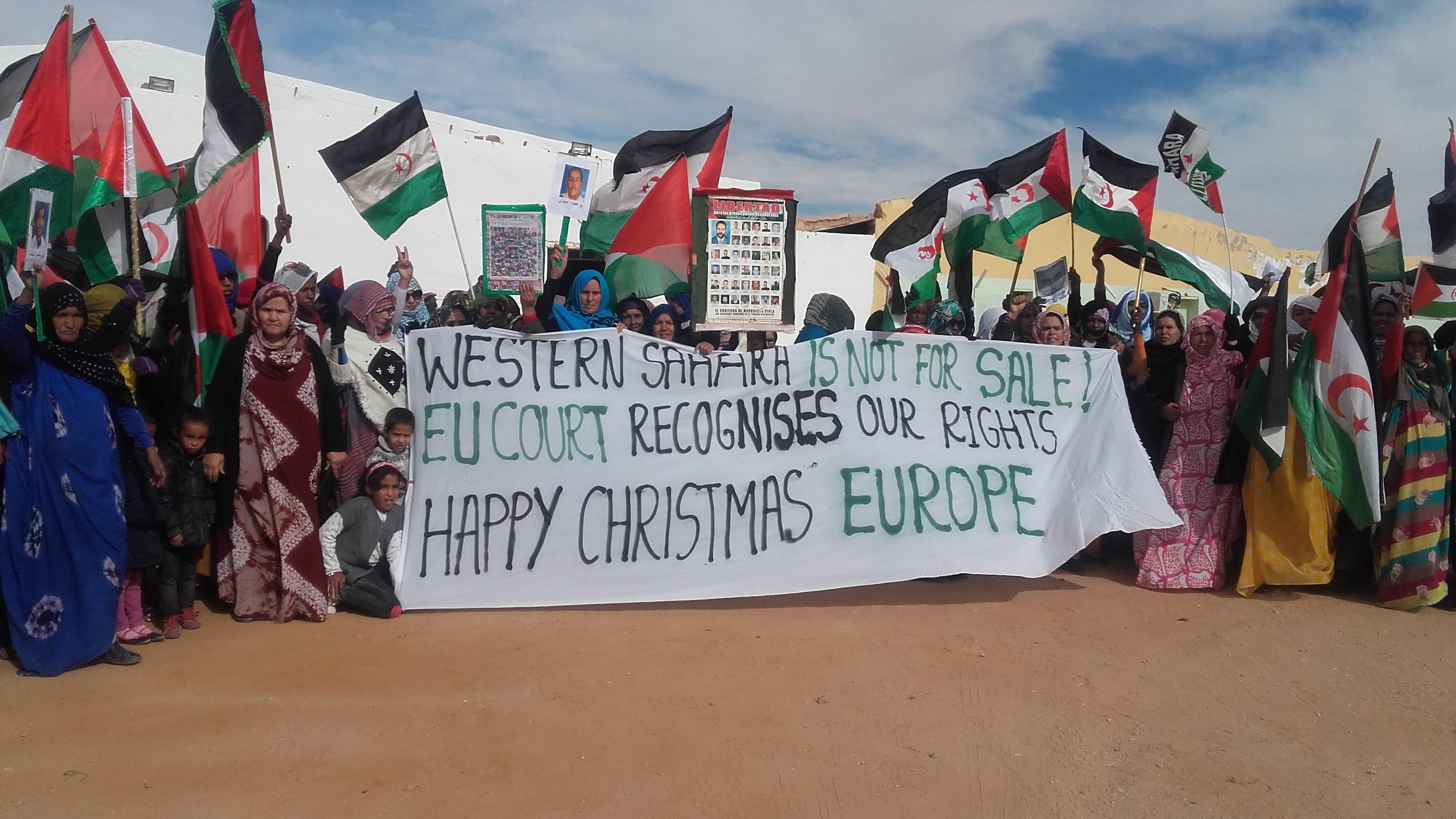 Es stehen eine Menge von Sahraouis in der Wüste im Halbkreis. Einige halten ein Transparent: Die Westsahara steht nicht zum Verkauf. Das EU-Gericht anerkennt unsere Rechte. Fröhliche Weihnachten Europa.