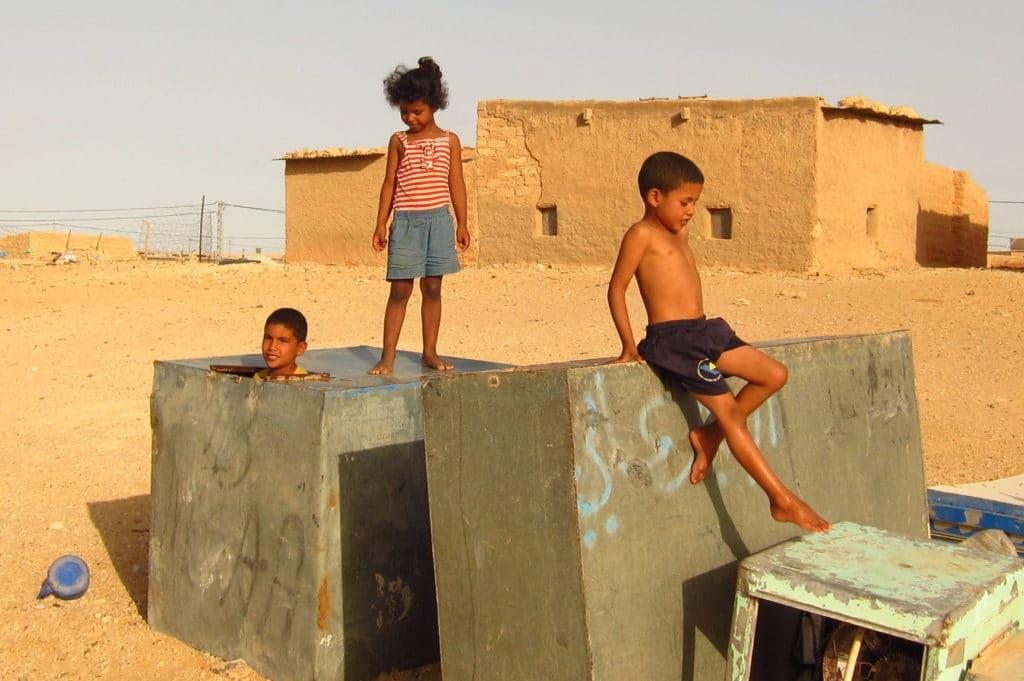 Kinder klettern auf alten, verrostetten Metallkisten herum die im Flüchtlingslager in der Wüste liegen.