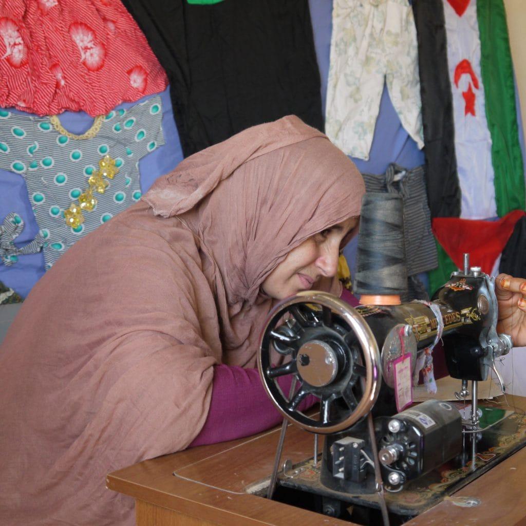 Junge Frau vor manuell betriebener Nähmaschine im Lager Smara.