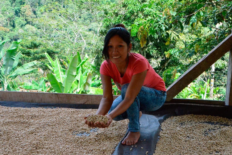 Eine junge Frau hält Kaffeebohnen in ihren Händen.