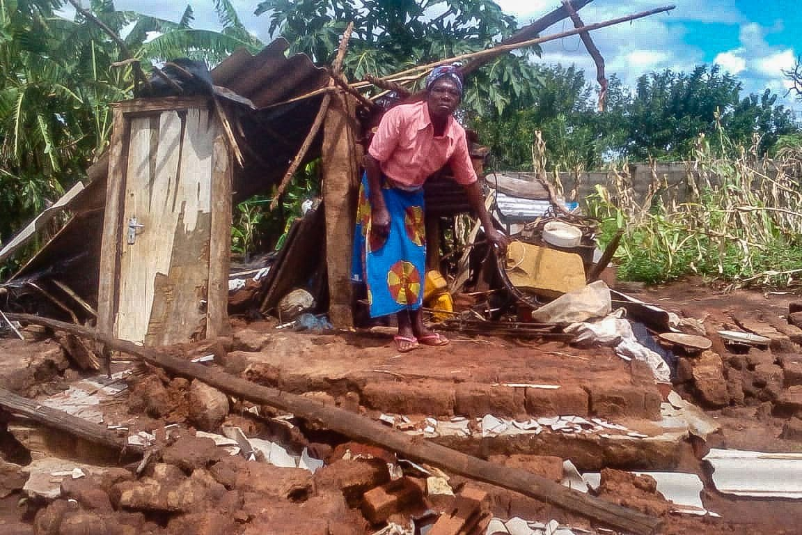 Black woman builds a temporary hut with pieces of corrugated iron.